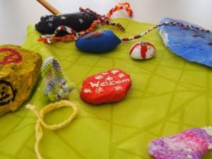 Liebevoll geflochtene Bänder und bemalte Steine als Deko und Gastgeschenke